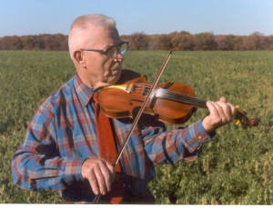 Les Raber fiddling a tune in the field behind his house.
